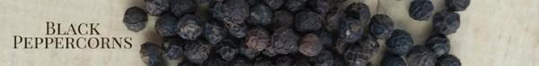 Black peppercorns on a wood board