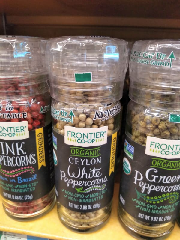 Frontier Co-OP Organic Peppercorns at the store in grinders. The varieties includes are pink peppercorns, Ceylon whit peppercorns, and green peppercorns.