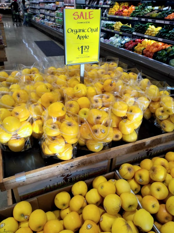A sale on bags of Opal apples at Whole Foods Market is shown. The apples are organic going for $1.79 per pound.