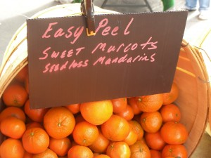 "A small basket of mandarins with a sign that says ""Easy Peel Sweet Murrcots Seedless Mandarins"""