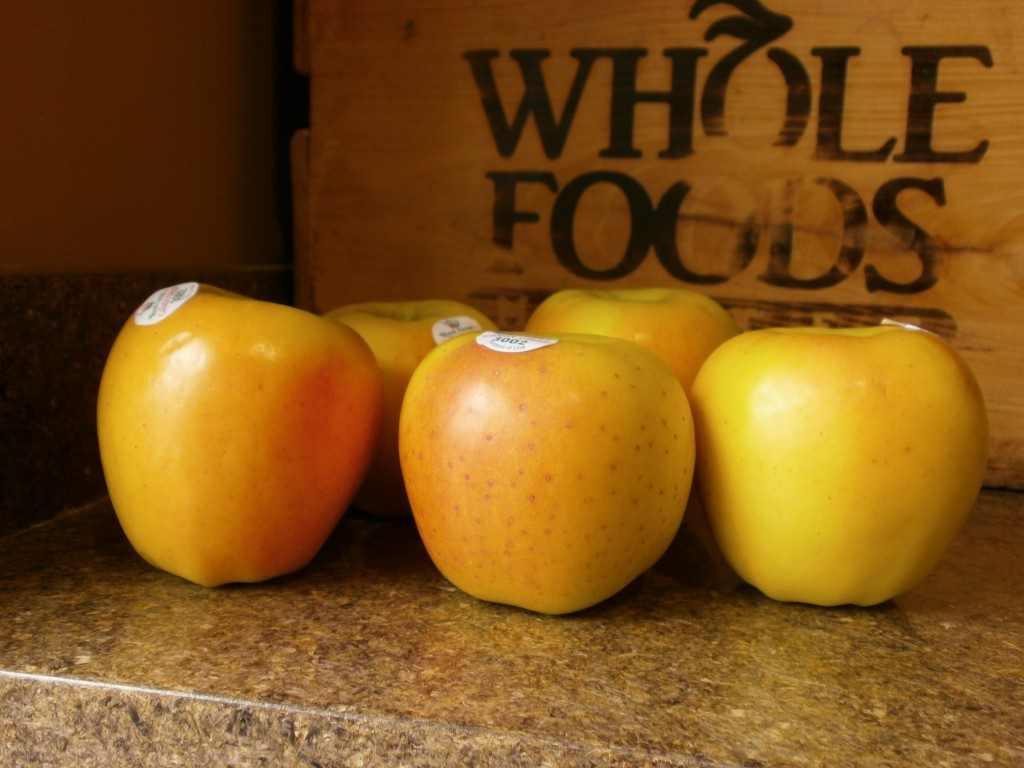 Five Candy Crisp apples sitting on a counter next to a bin that says Whole Foods Market on it.