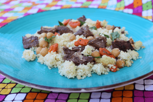 Moroccan style pot roast with beef, carrots, and Israeli couscous on a blue plate on top of colorful fabric.