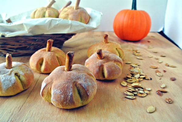 Pumpkin Yeast Rolls shaped into mini pumpkins with a pretzel on top for a steam are sitting on a wooden board with roasted pumpkin seeds and a whole pie pumpkin in the background.