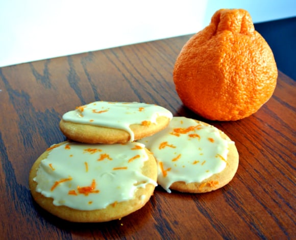 3 Sugar cookies with Sumo citrus juice, topped with a glaze that include Sumo citrus zest sitting on a table with a Sumo Citrus mandarin behind