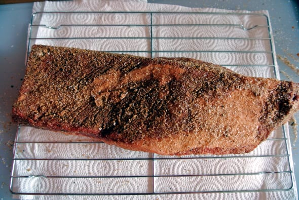 A seasoned brisket is shown on a cooling rack on top of a cutting board with a paper towel.