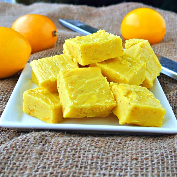 Meyer Lemon Fudge sitting on a white plate on top of a burlap cloth with Meyer lemons behind it.