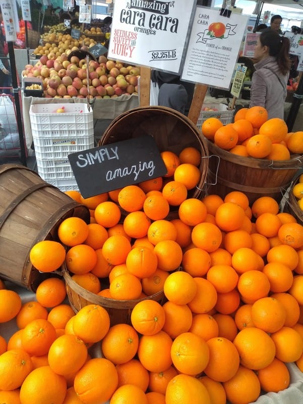 A display of Cara Cara oranges at a farmer's market with a sign that says simple amazing.