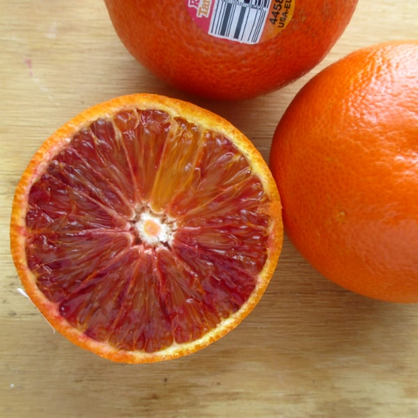 Three Ruby tango mandarins on a wood board with one of them sliced open to show the red interior.