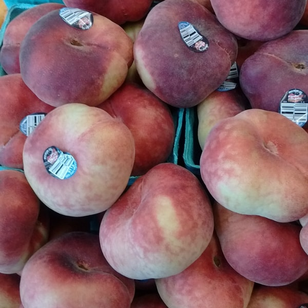 "A beautiful display of ""Flying Saucer"" donut peaches at Whole Foods Market in Ann Arbor, Michigan."