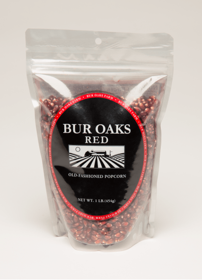A bag of Bur Oaks Red Popcorn in front of white background