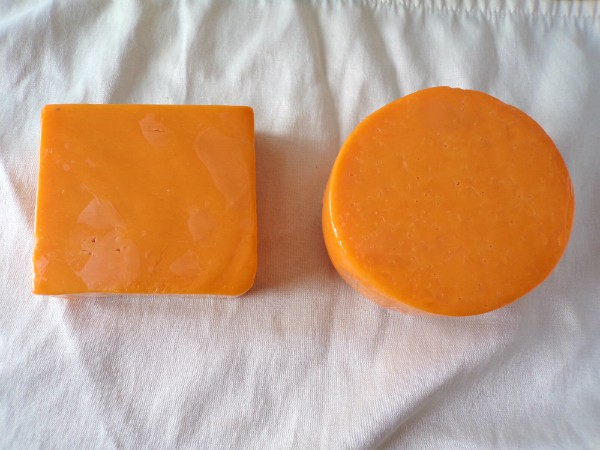 A square block of cheddar cheese next to a circle of colby cheese on a white towel.
