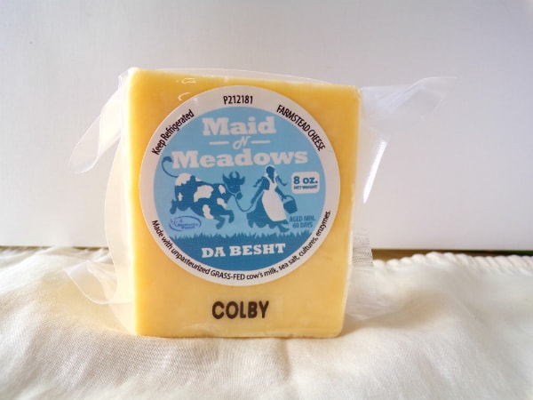 A block of Maid n Meadows Colby cheese on a white towel.