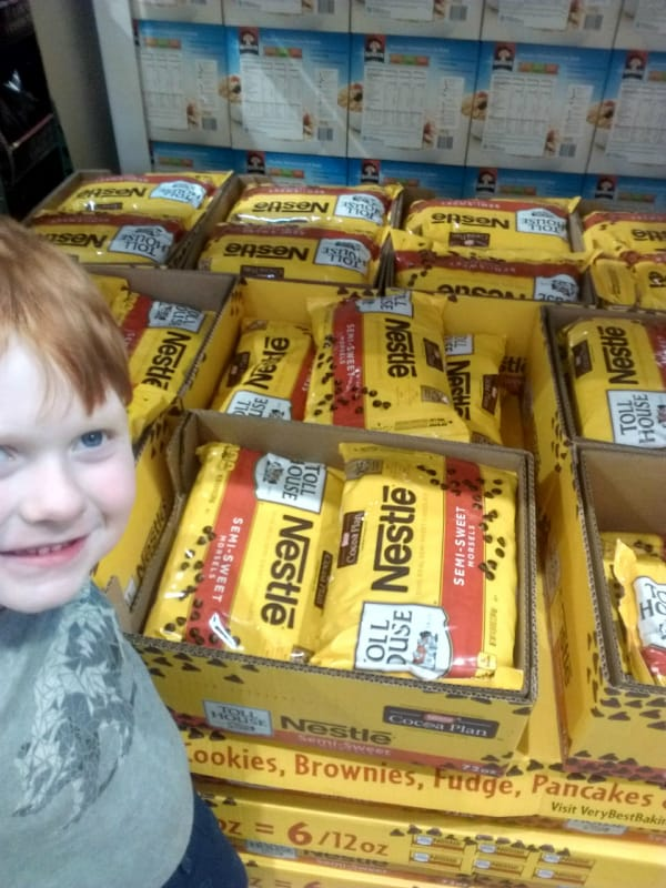 Boxes with bags of Nestle Semi-Sweet Morsels with my son standing to the left.