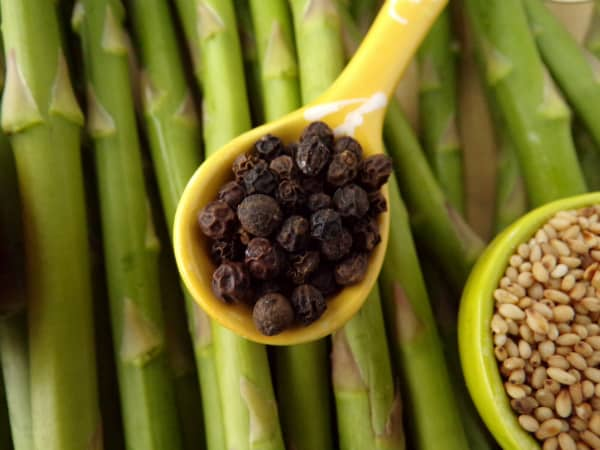 Spoon of black peppercorns on asparagus