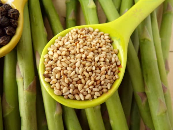 Spoon of sesame seeds on asparagus