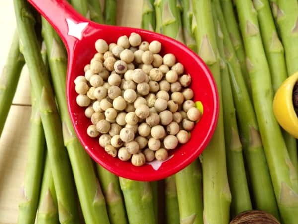 Spoon of white peppercorns on asparagus