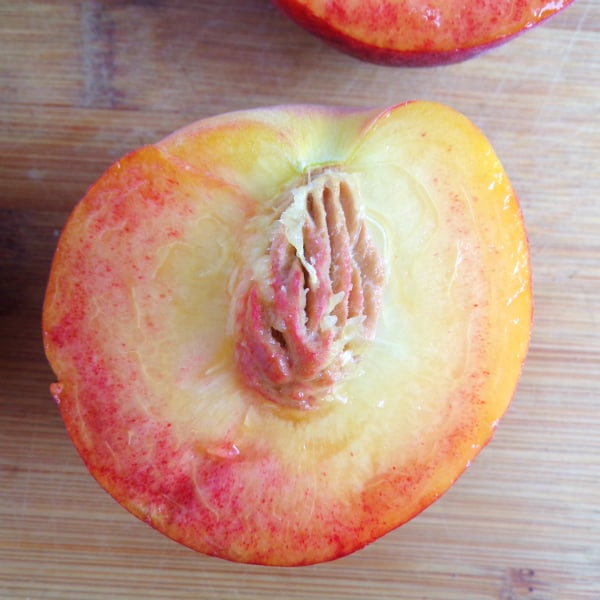 A single Blaze Prince peach with the pit still in the middle. the flesh of the peach has some red coloring in it.