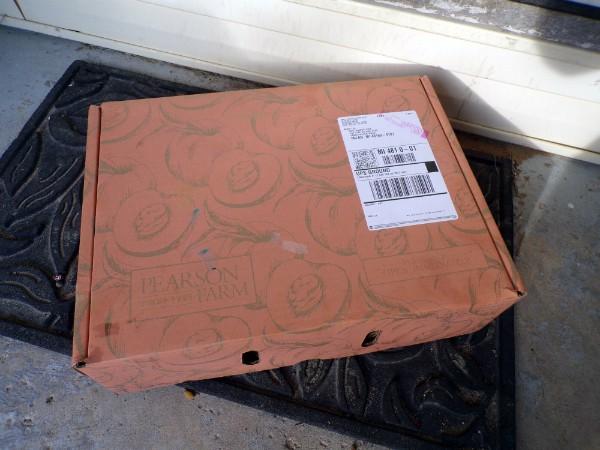 A box of Pearson Farm peaches sitting on a porch step