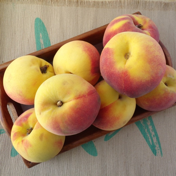 A wood tray full of peaches sitting on top of cloth placemat that is brown with streaks of turquoise.