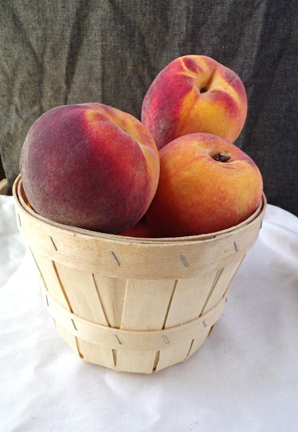Peaches sitting inside of a mini peach basket