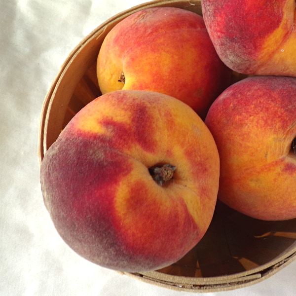 Overhead view of peaches inside a mini peach basket
