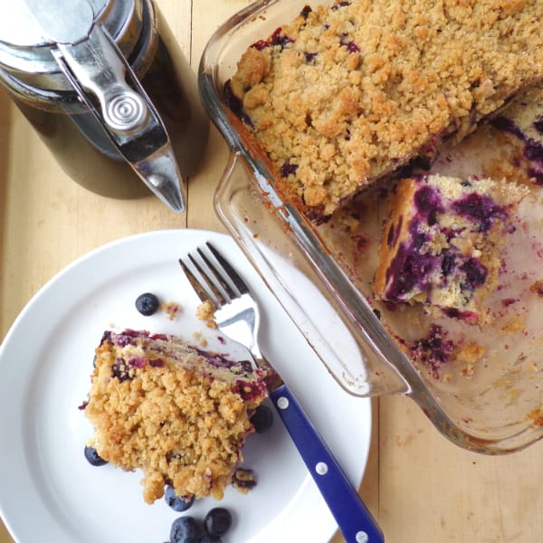 Blueberry Buckle slice on a plate with the buckle in a glass pan next to it. A bottle of maple syrup is located nearby as well.