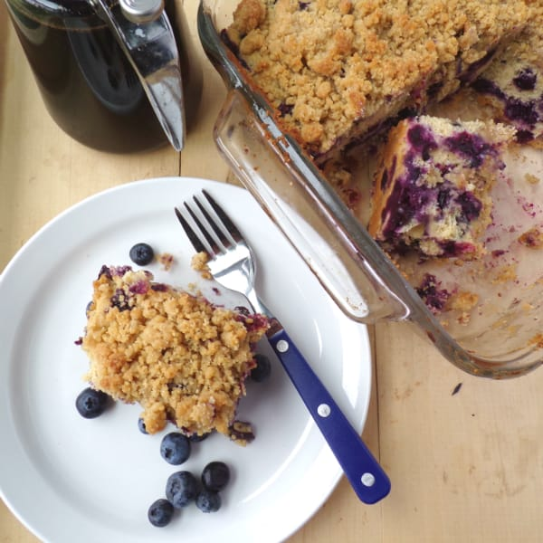 A picture of Maple Blueberry Buckle with a slice sitting on a white plate