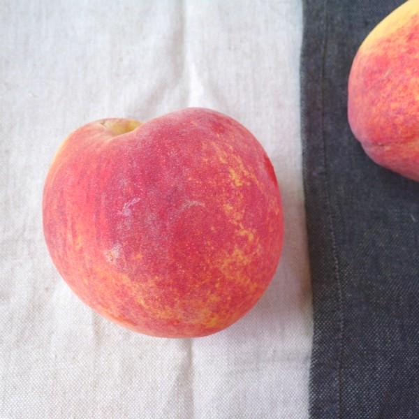 A single Flame Prince peach sitting on a white towel next to a single Flame Prince peach on a black towel