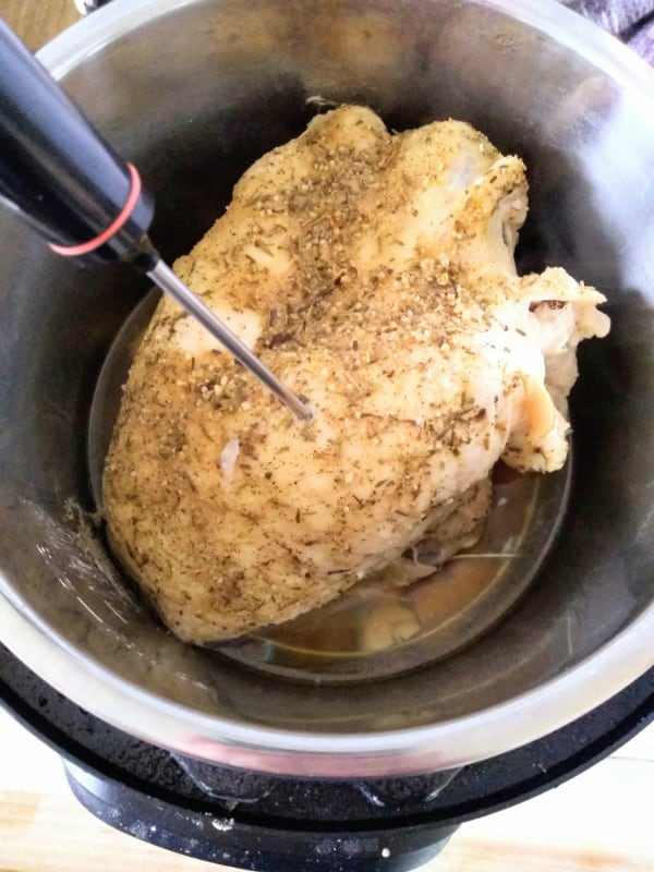 A bone-in turkey breast inside the Instant Pot with a instant read thermometer checking the temperature