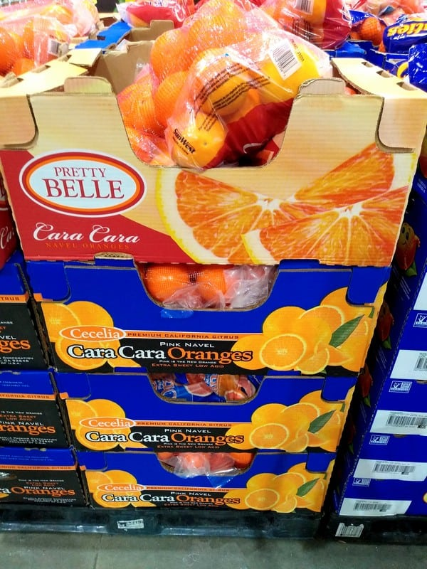 A display at Costco with different boxes of Cara Cara oranges. The top says Pretty Belle and the bottom boxes are from Cecelia.