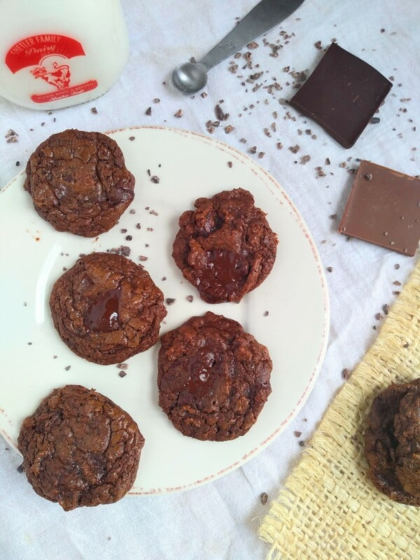 Alton Brown's Chocapocalypse cookies on a white plate with chocolate squares next to it and a glass bottle of milk.