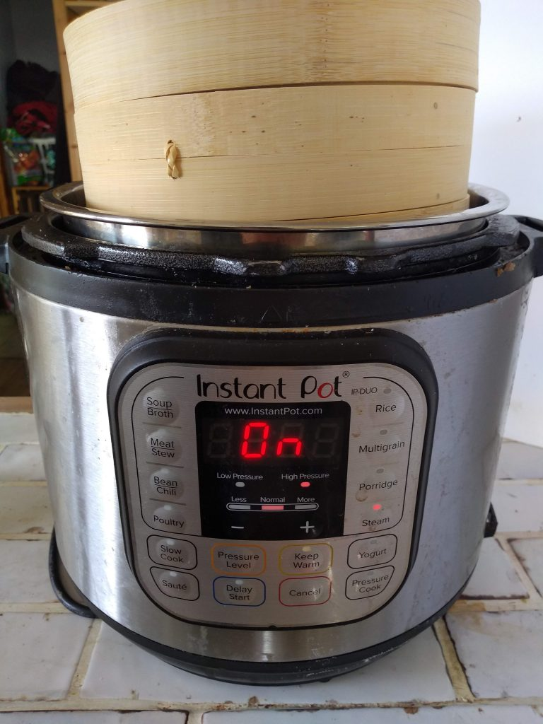Instant Pot with a bamboo steamer on top of it