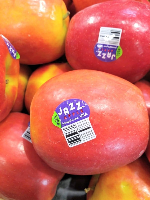 Close up view of a Jazz apple with the new PLU sticker on it, with several apples in the background