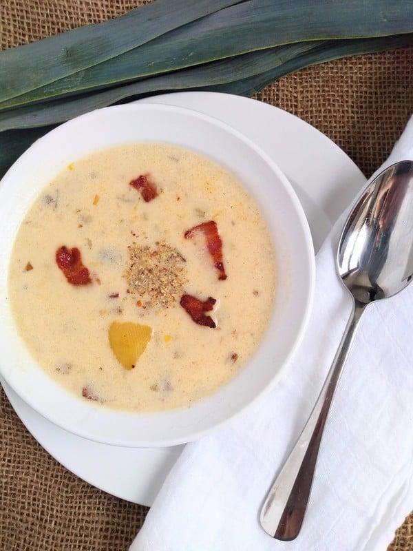 Alton Brown's Potato Leek Soup served in a white bowl with bacon