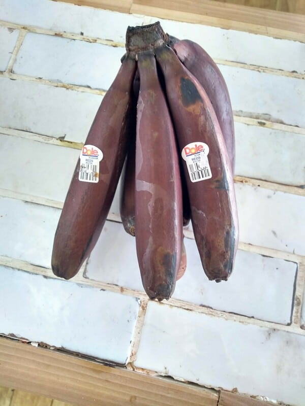 A bunch of Dole red bananas sitting on a white countertop.