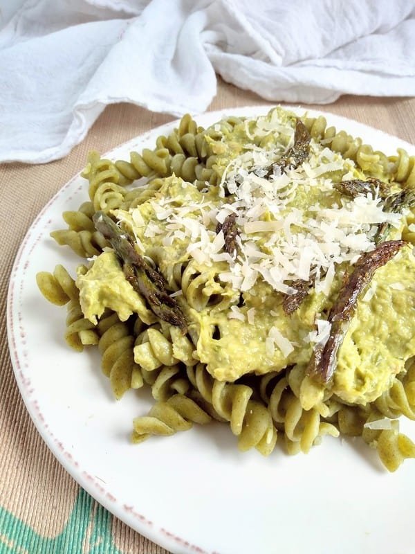 A plate of seaweed pasta covered in a Asparagus pesto sauce with shaved parmesan on top and asparagus tips. The plate has a brown line around the edge and is sitting on a brown place mat.