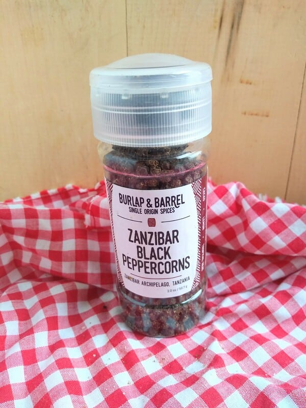 Burlap & Barrel Zanzibar Black Peppercorn grinder in front of a wood board with a red/white checkered cloth underneath.
