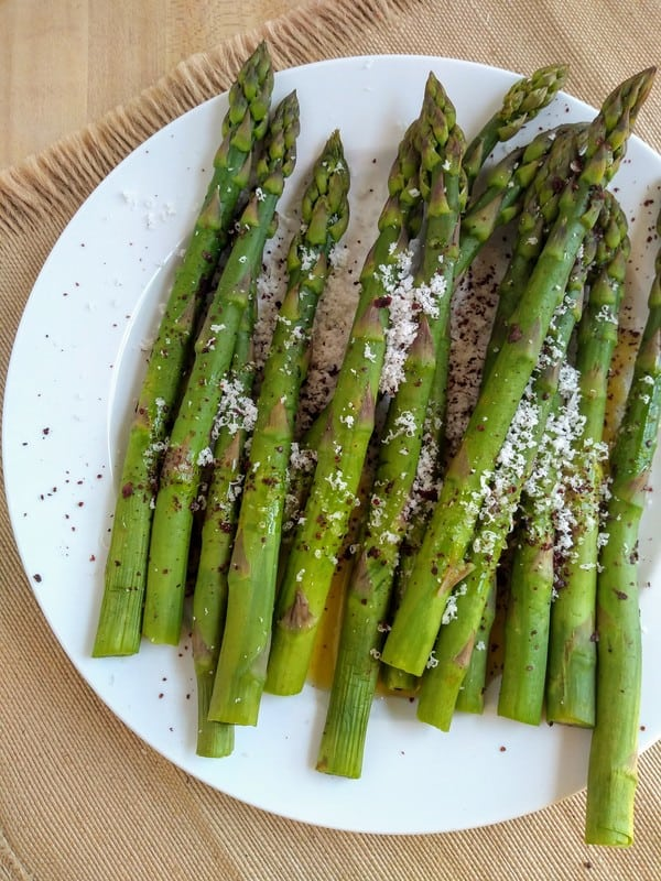 Plate of asparagus with romano cheese and sumac on top