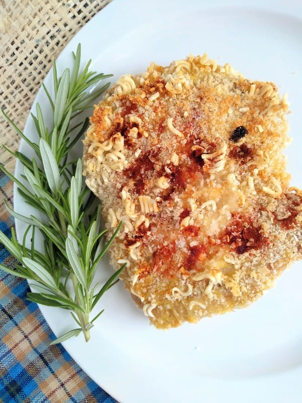 Panko and crushed ramen breaded pork chops on a plate with some rosemary
