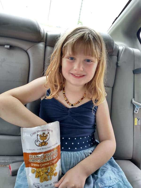 My daughter sitting in the back seat of the car eating a bag of Crazy Monkey Baking Peanut Butter Chocolate Chips granola.