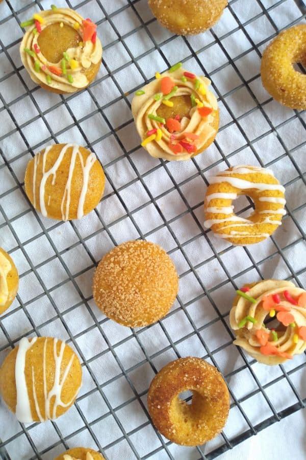 Decorated pumpkin donuts with cinnamon sugar, vanilla drizzle, or pumpkin buttercream frosting