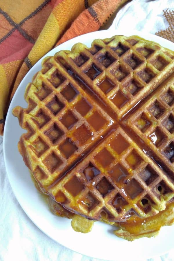 Pumpkin Overnight Yeast Waffles on a plate with syrup