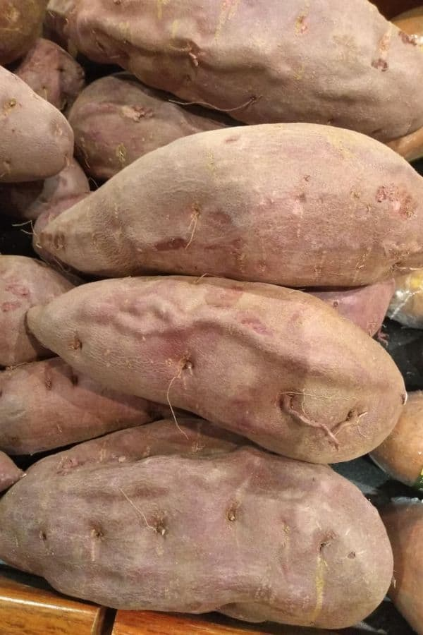 A grocery store display of Purple Sweet Potatoes that are purple inside and out.