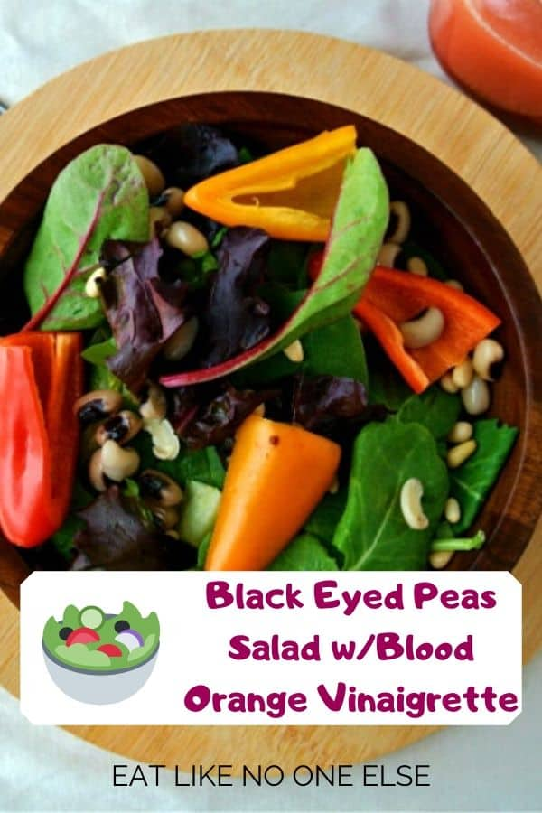A salad with black eyed peas, spring mix, and bell peppers in a wood bowl.