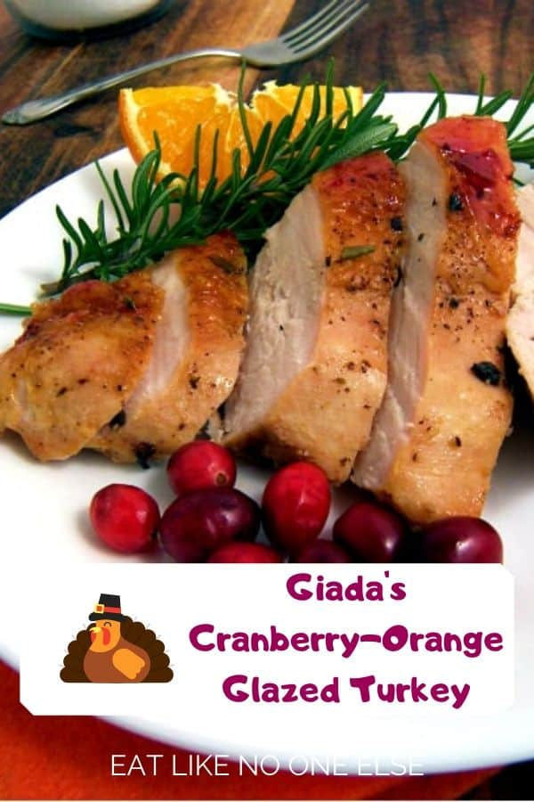 Sliced up pieces of turkey breast on a white plate with a slice of orange, rosemary, and cranberries