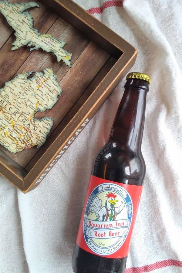 A bottle of Frankenmuth Bavarian Inn Root Beer next to a wood Michigan map.