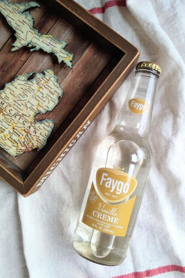 A bottle of Faygo Vanilla Creme next to a wood Michigan map.