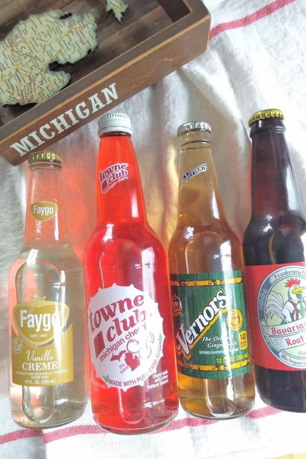 Glass bottle of soda pop, from left to right, Faygo Vanilla Creme, Towne Club Michigan Cherry, Vernors, and Frankenmuth Bavarian Inn Root Beer.