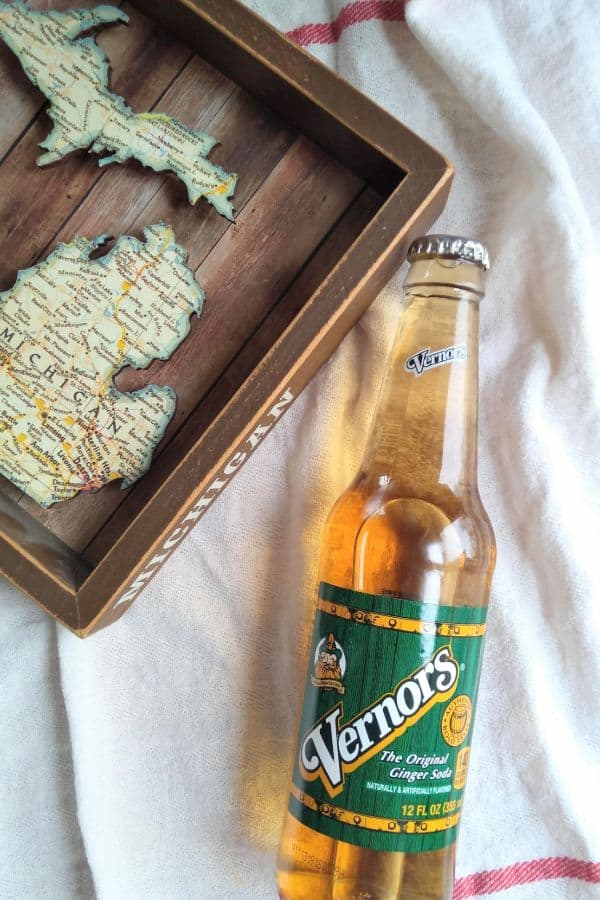 A bottle of Vernors next to a wood Michigan map.