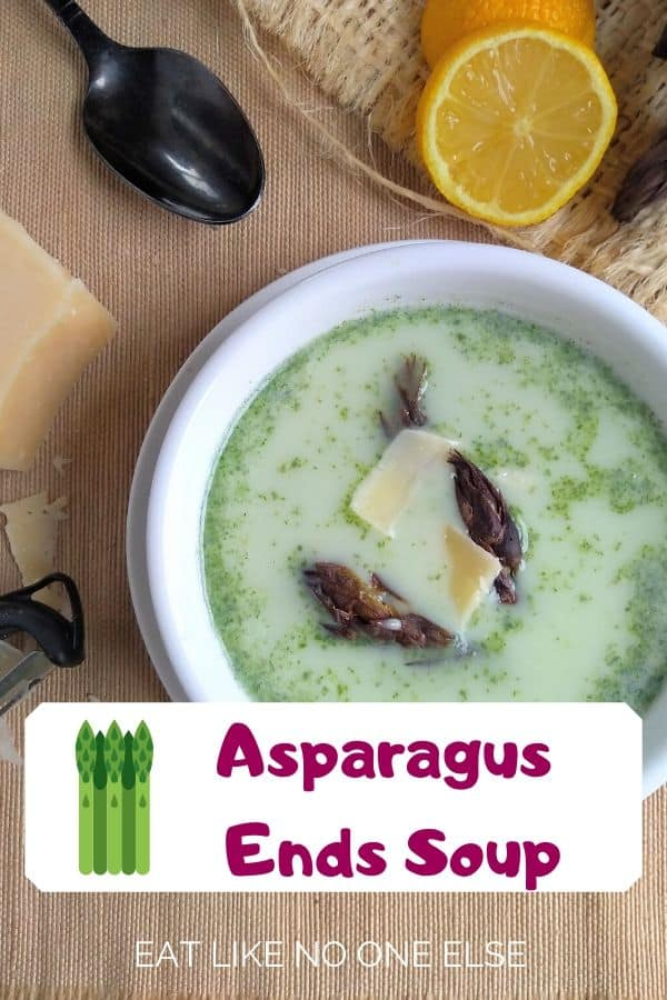Asparagus Ends Soup in a white bowl with a black spoon and lemon wedge in the background